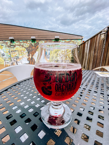 Urban Orchard Cider Asheville NC with red cider in glass on outdoor table with mural and cloudy sky in the background