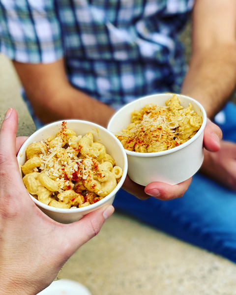 Asheville VeganFest Mac and Cheese with two takeaway containers of vegan mac and cheese with red seasoning
