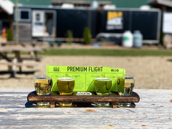 Bold Rock Cidery Asheville Mills River NC premium flight with four flight glasses filled with golden and yellow colored cider outside on picnic table