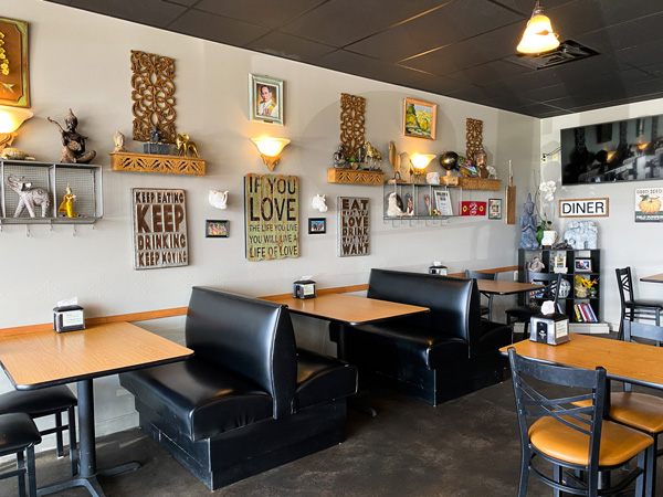 Boon Choo Thai Express Restaurant with short booth tables and signs on wall with cute and fun food sayings