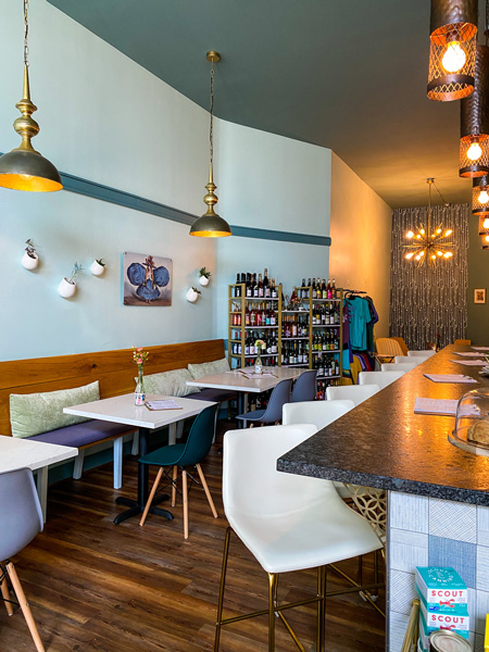 Botanist and Barrel Mead Cider Asheville NC with blue walls, tables, bar with white bar chairs and trendy lights