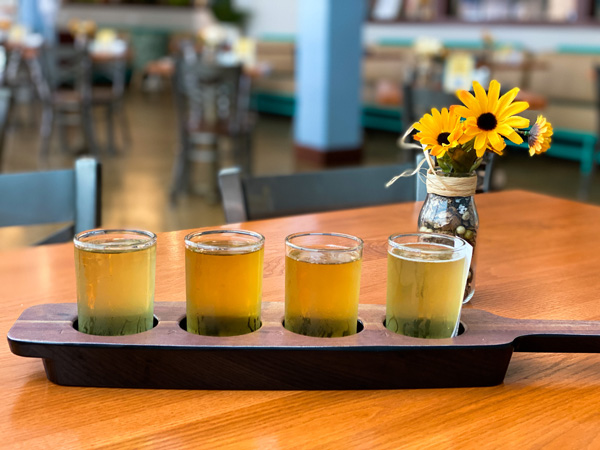 Flight Noble Cider Asheville NC with four light to yellow colored ciders in wooden flight with yellow flowers in vase on table