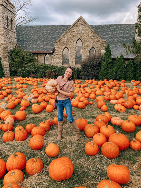 Grace Episcopal Church Asheville Pumpkin Patch with white brunette woman in pink top and jeans holding white-orange pumpkin
