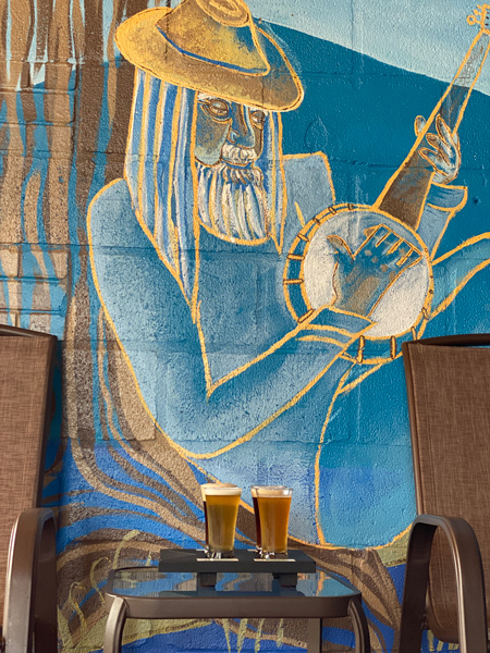 Guidon Brewing Company Hendersonville NC with blue mural of older man with beard and hat playing the banjo and flight of light beers on a table