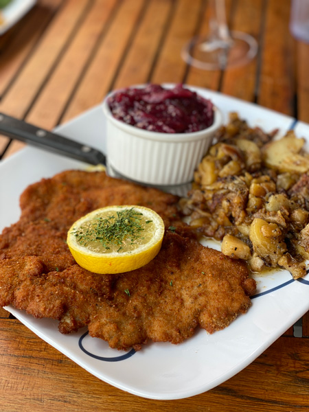 Haus Heidelberg German Restaurant Hendersonville with breaded schnitzel on plate with fried potatoes and red cabbage garnished with lemon slice