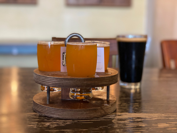 Oklawaha Brewing Company Hendersonville NC beer flight with light beers next to a dark cider