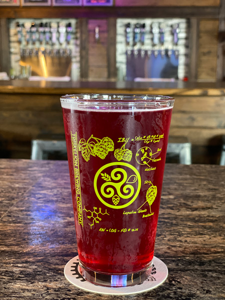 Triskelion Brewing Hendersonville Brewery red cider in beer glass with bar blurred in background