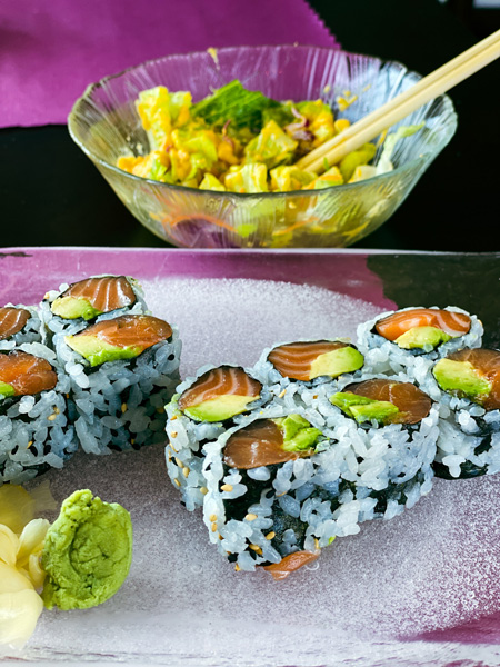 Umi Sushi Hendersonville NC with salmon and avocado sushi rolls and salad with ginger dressing and chopsticks