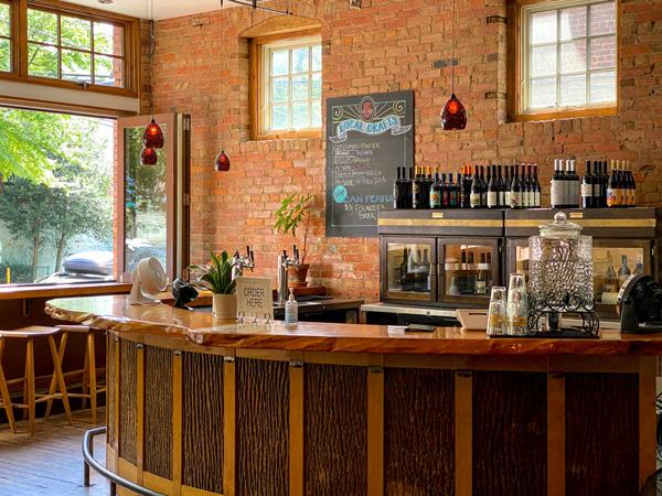 5 Walnut Wine Bar Asheville NC with dark wooden bar, brick back wall, menu, and wine bottles