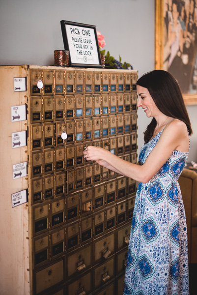 Asheville Rooftop Bars Top of the Monk with white brunette woman in long white and blue dress using a key to open a card catalog