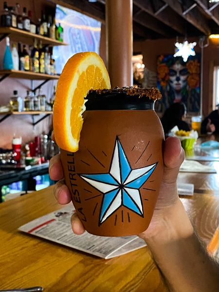 Asheville tacos Ay Caramba Mexican Grill with white handing holding up drink in clay glass with white and blue star and garnished with an orange