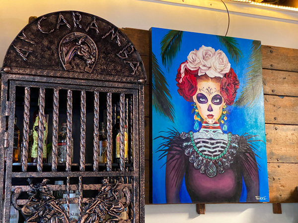 Ay Caramba Mexican Grill with picture of liquor cabinet and Day of Dead painting on wall
