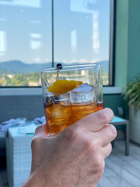 Best Rooftop Bars Asheville Capella On 9 with white hand holding up an Old Fashioned Craft cocktail in front of window with view of Blue Ridge Mountains