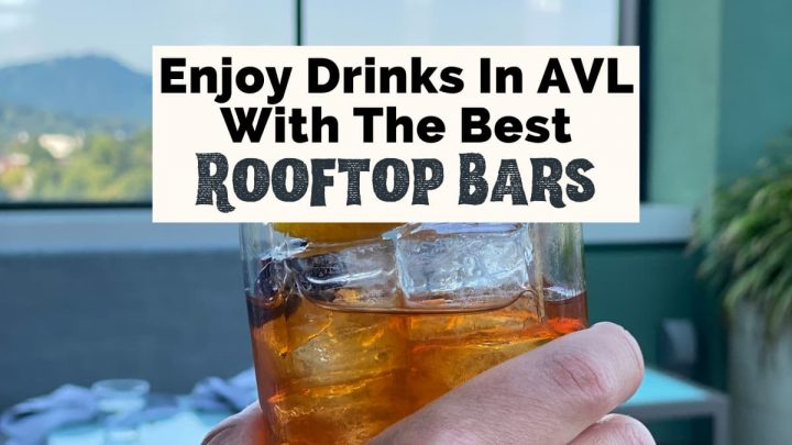 Best Rooftop Bars In Asheville NC Capella On 9 with white hand holding up an Old Fashioned Craft cocktail in front of window with view of Blue Ridge Mountains