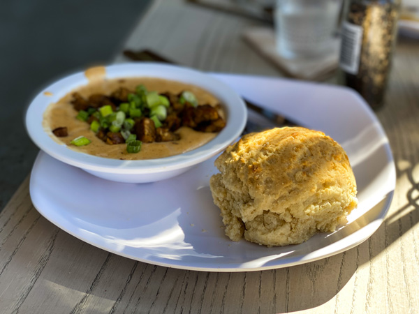 Biscuit Head Asheville Breakfast with biscuit and vegan cheese gravy and sausage on white plate