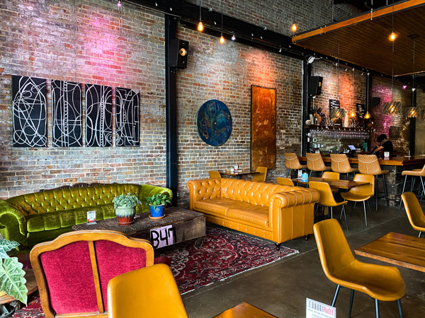 Bottle Riot Wine Bar Asheville with yellow and green couches, purple rug, and pink chair with bar