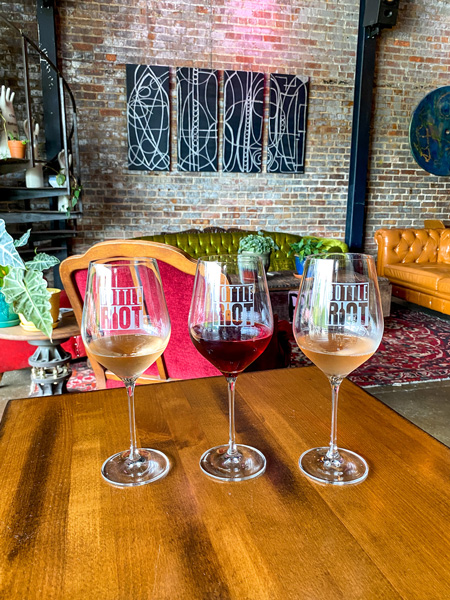 Bottle Riot Wines Asheville with three glasses of half-pour red and white wines on table