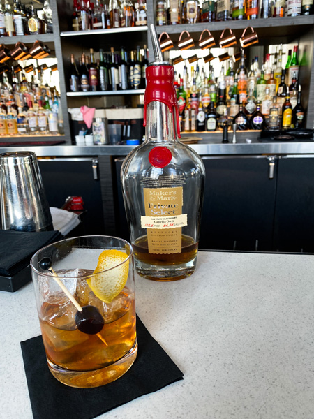 Capella On 9 Rooftop Bar Asheville NC with Maker's Mark Bourbon on bar next to classic Old Fashioned craft cocktail