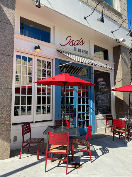 Isa's French Bistro Breakfast Brunch in Downtown Asheville with blue doors, white facade, and red tables with umbrellas