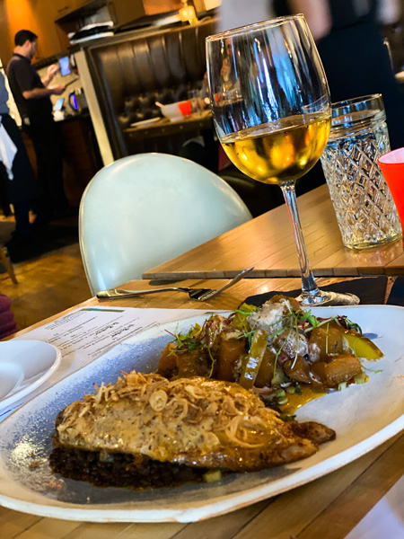 Jargon Fine Dining Restaurant in West Asheville NC with plate of chicken covered in sauce with roasted potato side and glass of white wine