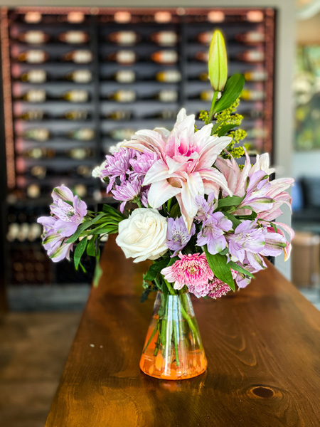 Marked Tree Vineyard Downtown Asheville Wine Bar with purple, white, and pink flowers on table