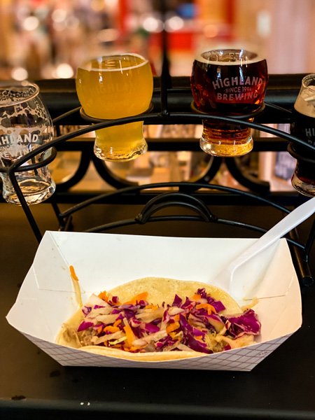 Peace Love Tacos Downtown Asheville NC with Highland beer flight behind tacos with cabbage and pork