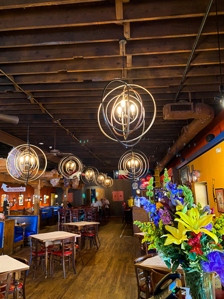 The Cantina Mexican Restaurant Asheville NC with picture of circular lights, colorful flowers, and tables