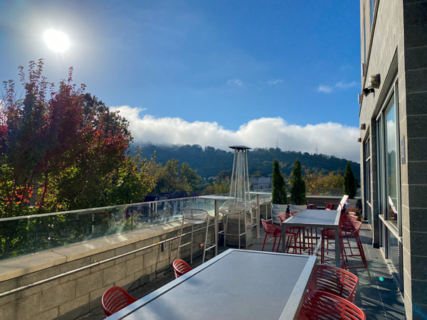The Ledge Aloft Rooftop Bar Asheville with silver tables and red orange chairs with fall foliage, blue sky, and sun