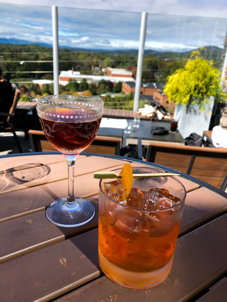 The Montford Rooftop Bar Asheville with two cocktails on a table overlooking the mountains