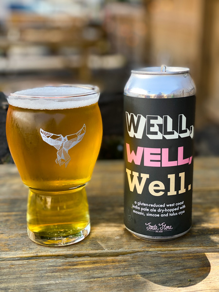 The Whale Beer in West Asheville with glass oof amber gluten free beer next to can that says 'well. well. well.'