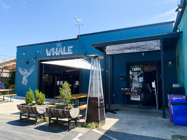 The Whale West Asheville North Carolina with blue building with patio, umbrella, and chairs with whale tail mural on wall
