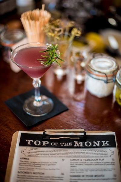 Top Of The Monk Rooftop Bar Asheville NC with picture of menu and pink cocktail garnished with rosemary