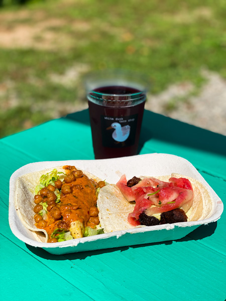 White Duck Taco Asheville NC with picture of two tacos and local craft cider on green picnic table