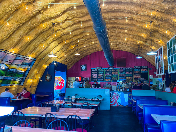 White Duck Taco Shop River Arts District Asheville, NC with menu of tacos, big wall, yellow ceilings with lights, and colorful tables