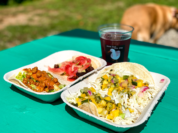 White Duck Taco Shop Asheville Tacos with Ginger Revenge ginger beer and four soft shell tacos on green picnic table outside