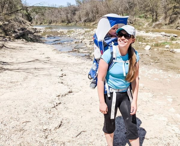 Tori Curran Explore With Tori white woman with long dirty blonde hair in light blue shirt with baby in hiking pack on back